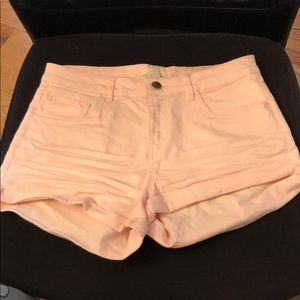 Light pink jean shorts.
